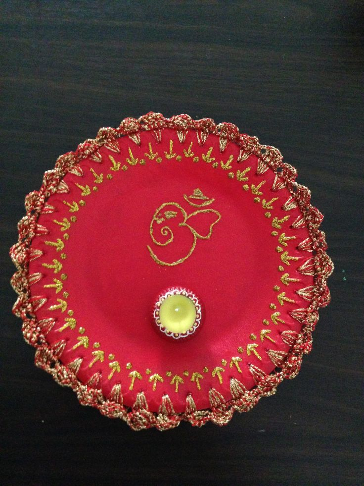 Pooja Thaali - 2 thermacol plates glued together....then coloured it using red fabric paint .....inserted holes at equal distance at the edge.....crocheted a border lace with gold & red yarn & then used gold glitter to design it....outline Ganesha with glitter at the top center of the plate with a diya....