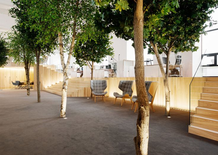 """KAMP Arhitektid has installed angular wooden rooms and trees inside a former factory, to create an office modelled on a """"bright summer forest""""."""