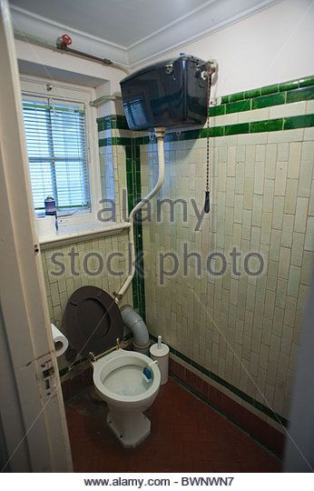 Old Victorian toilet in a dingy closet with Victorian tiles flooring and overhead cistern - Stock Image