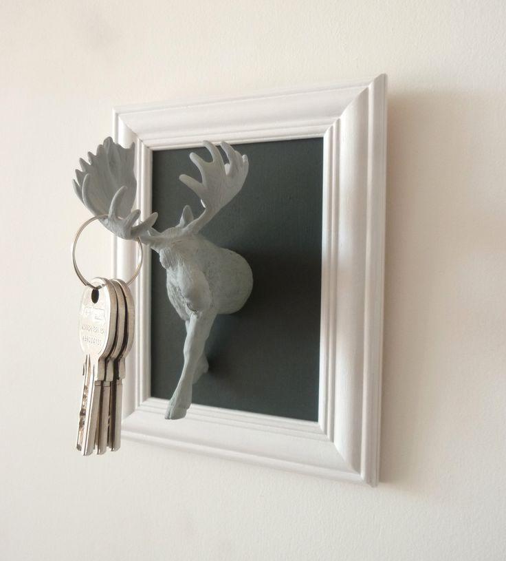 Accroche-clés : élan gris clair sur fond gris foncé et cadre blanc