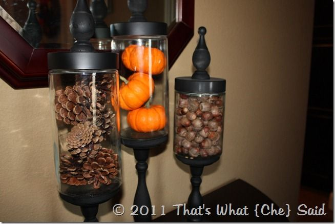 One jar is filled with pinecones, one with small pumpkins, and one with acorns.