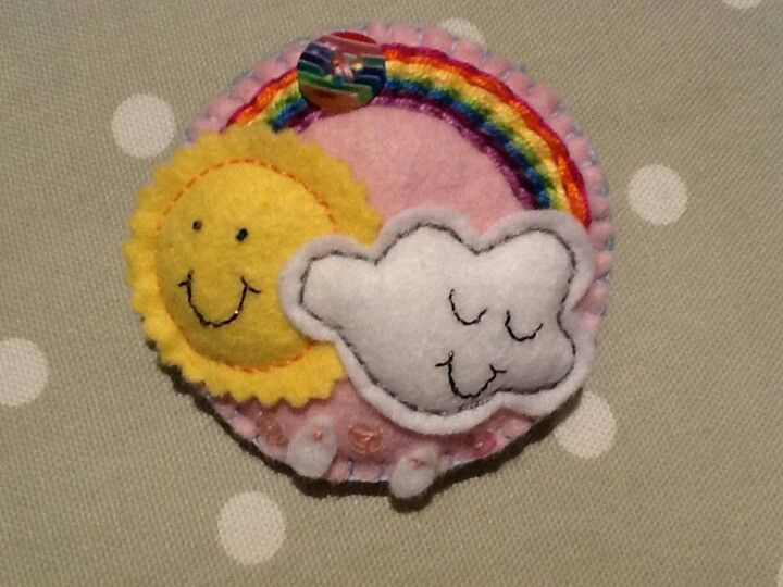 Handmade felt rainbow brooch in pink, with embroidery, sequins and button embellishments.