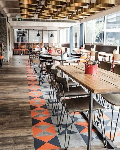 Wednesday Tile Inspiration! Featured today is a cool raw urban space that oozes personality! It radiates warmth and has a true charm to it. This Bonfire restaurant located in London is captivating with patchwork floor tiles in navy orange and grey helping to divide the space into different zones breaking up the floor plate. We also love the use of timber tiles  how realistic do they look?! Apply this concept to your home or interior project  breaking up your floor with different patterned…