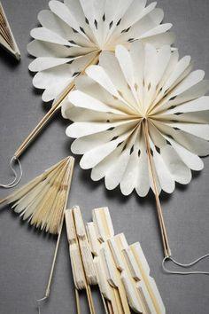 Il s'agit de deux fleurs en origami. Les fleurs sont blanches avec des lignes noirs. Il y a encore une fois des dimensions qui rendent l'ilustration très intéressante. Il n'y a pas de couleur vives.. Il n'y a pas non plus de couleur foncées. Il n'y a que du blanc, du gris pâle et du jaune pâle/blanc crème.