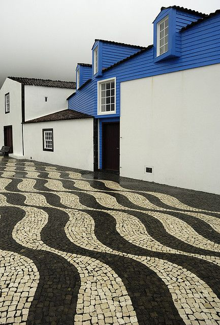 Black and white wave patterned traditional mosaic sidewalk in Lajes, a former Azorean whaling village - Portugal