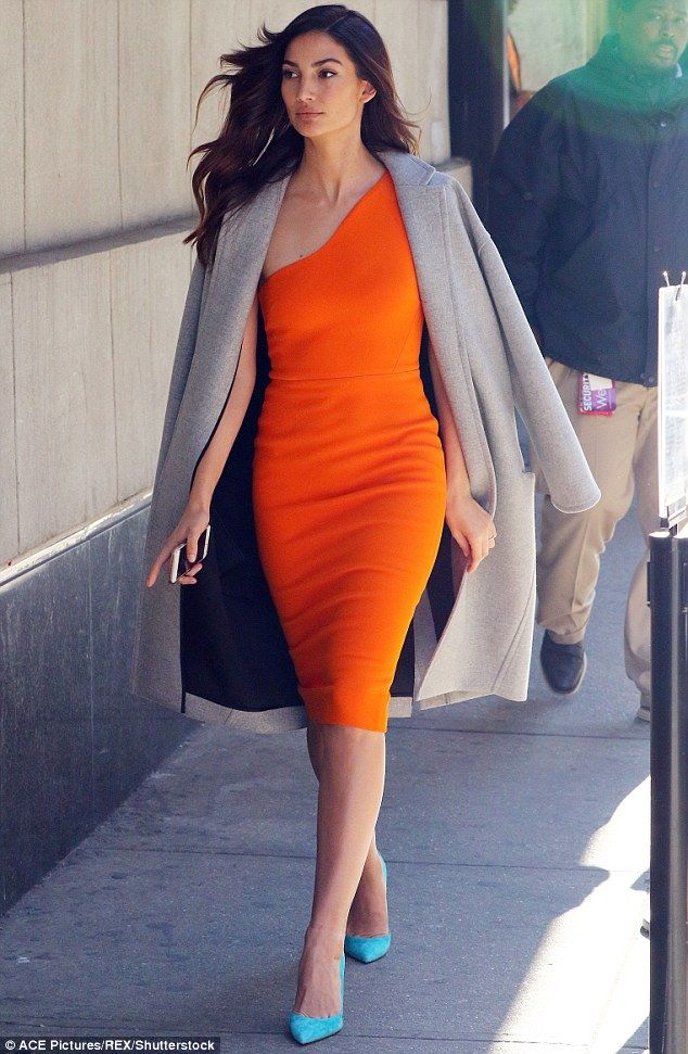 A dream in tangerine: The model started out her day in a slinky one-shouldered orange dress with bright blue pumps and a soft grey coat