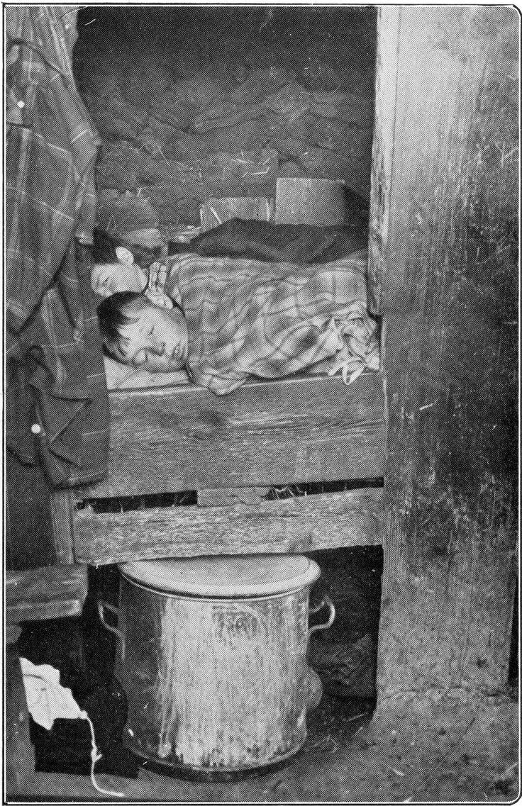 Kinderen slapen in een soort van bedstee in een krotwoning [plaggenhut] te Drente, o.a. gemaakt van turf. Maart1929. Let op! het origneel van deze foto bevat een raster.