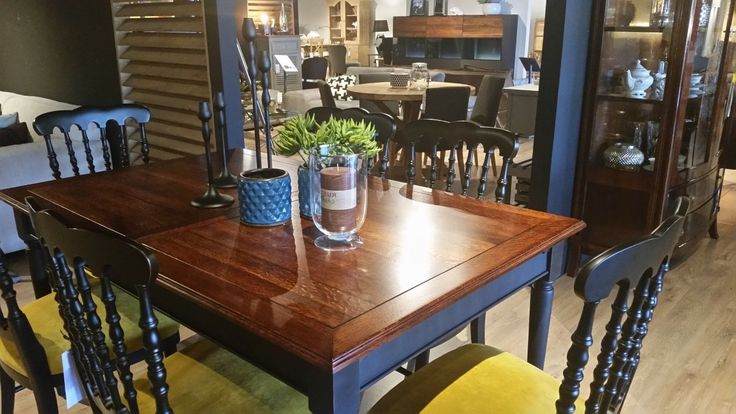 Komplet jadalniany dla 6 osób: drewniany stół z połyskującym blatem w naturalnym kolorze drewna oraz czarnymi nogami. Krzesła z tapicerowanym siedziskiem w kolorze żółtym i drewnianym prętowym oparciem.