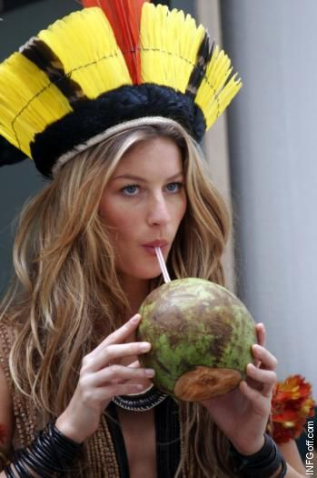 Gisele Bundchen wears an interesting headdress and drinks out of a coconut while visiting the Xingu Republic in Brazil in November 2006.