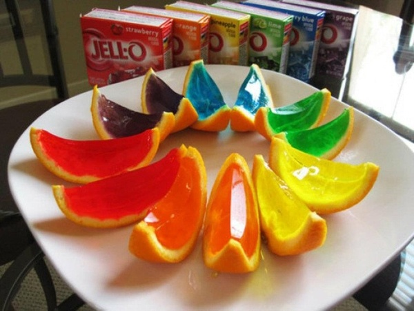 Cut oranges in 1/2 and hollow out.  Set hollowed orange halves, open side up, in something secure so they don't move around when the jello is in them (I used muffin pans). Prepare jello with 1/3 less water needed for recipe. Pour into orange halves. Set in fridge and chill completely. Take out of fridge, flip over onto cutting board (open side down so it's flat on the surface). Cut into slices, either halves again (1/4 of the whole) or into 3 slices. And voila! You have jello orange slices…