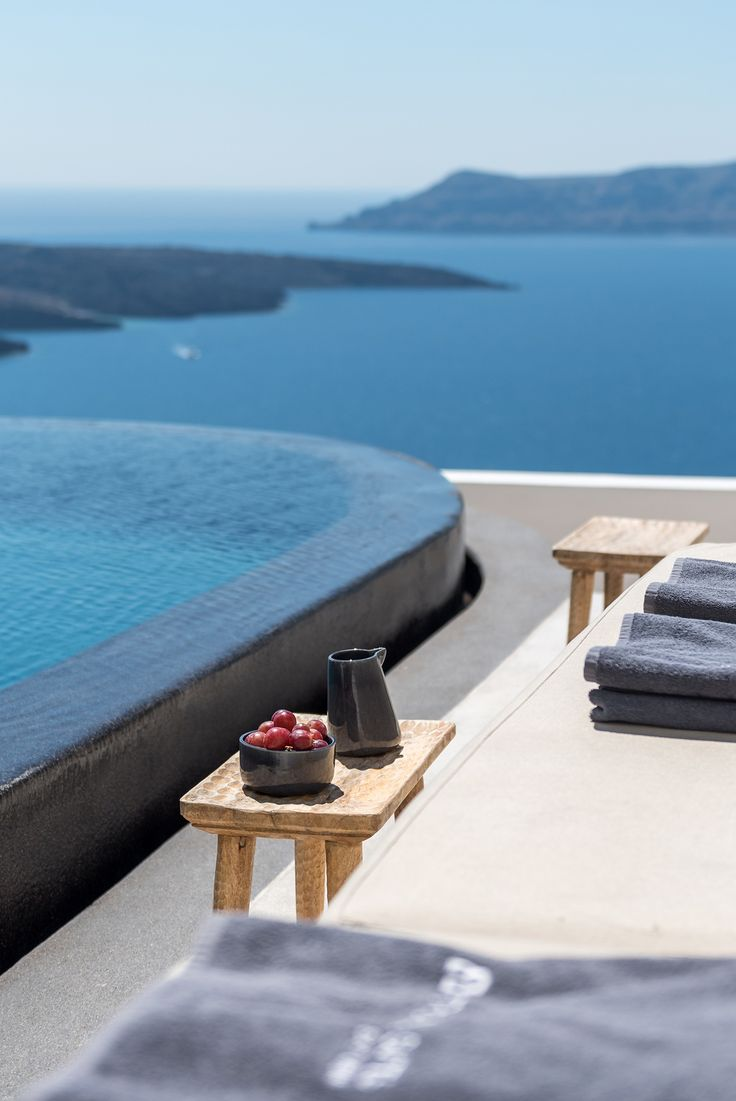 Beautiful black infinity pool on the terrace of luxury boutique hotel in Santorini, overlooking the sea and islands - aboratorium renovate seven suites at Porto Fira luxury hotel in Santorini, Greece. Luxury hotel designs feature on the www.martynwhitedesigns.com interior design blog.