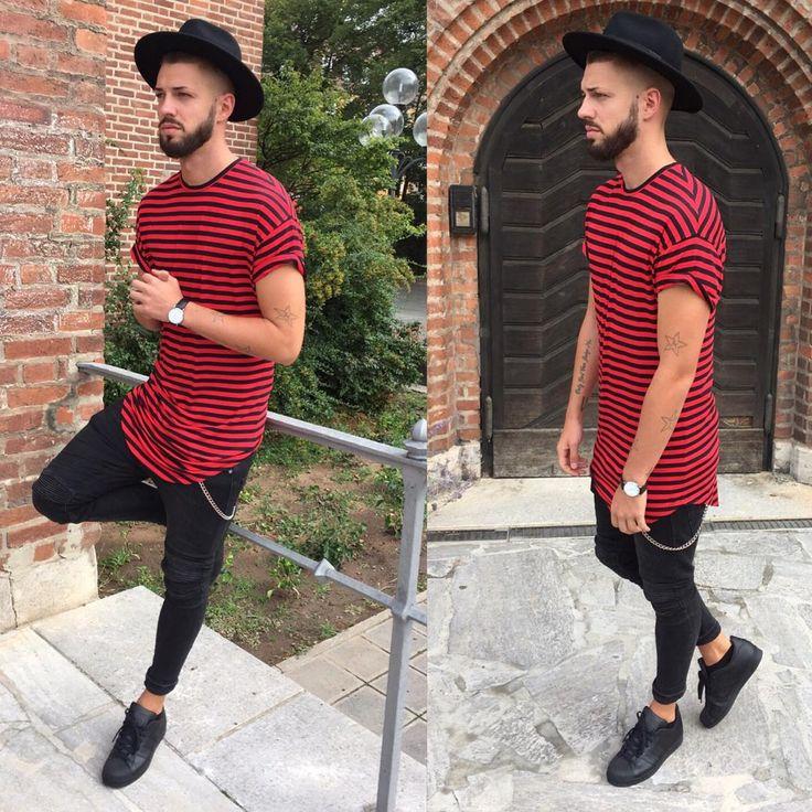 Zwarte, wollen hoed. Long fit t-shirt met rood en zwarte strepen. Zwart en wit horloge. Zwarte skinny jeans, en zwarte, lage sneakers.