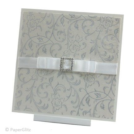 WHITEHAVEN  A delicate design using the exquisite embossed silver Olivia white pearl paper. It is finished off with a luxurious 15mm white double bow and a square diamante buckle. The inside text is printed on Ice Gold card and the invitation comes with a matching envelope. Price: $7.95 https://www.facebook.com/NextChapterWeddingInvitations