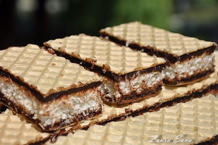 Va povesteam aici, la Painea umpluta, ce sfarsit de saptamana minunat am avut si cu cate retete bune ne-am delectat. Ei bine, printre ele s-a aflat si aceasta prajitura cu foi de napolitana, blat de cocos si crema de ciocolata, absolut delicioasa!!! Cele mai reusite napolitane cu nuca de cocos si ciocolata din lume :)) Ingrediente: - 2 foi mari de napolitana Blat de cocos: - 6 albusuri - 150 g. zahar tos - 150 g. nuca de cocos (fulgi uscati) - 1 lingura cu varf faina - 1 lingurita rasa praf…