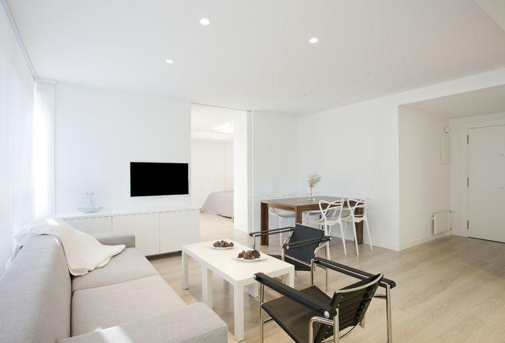 Reforma con predominio del blanco y la calidez de la madera. La decoración en tonalidades beiges y grises crea un ambiente moderno y acogedor.