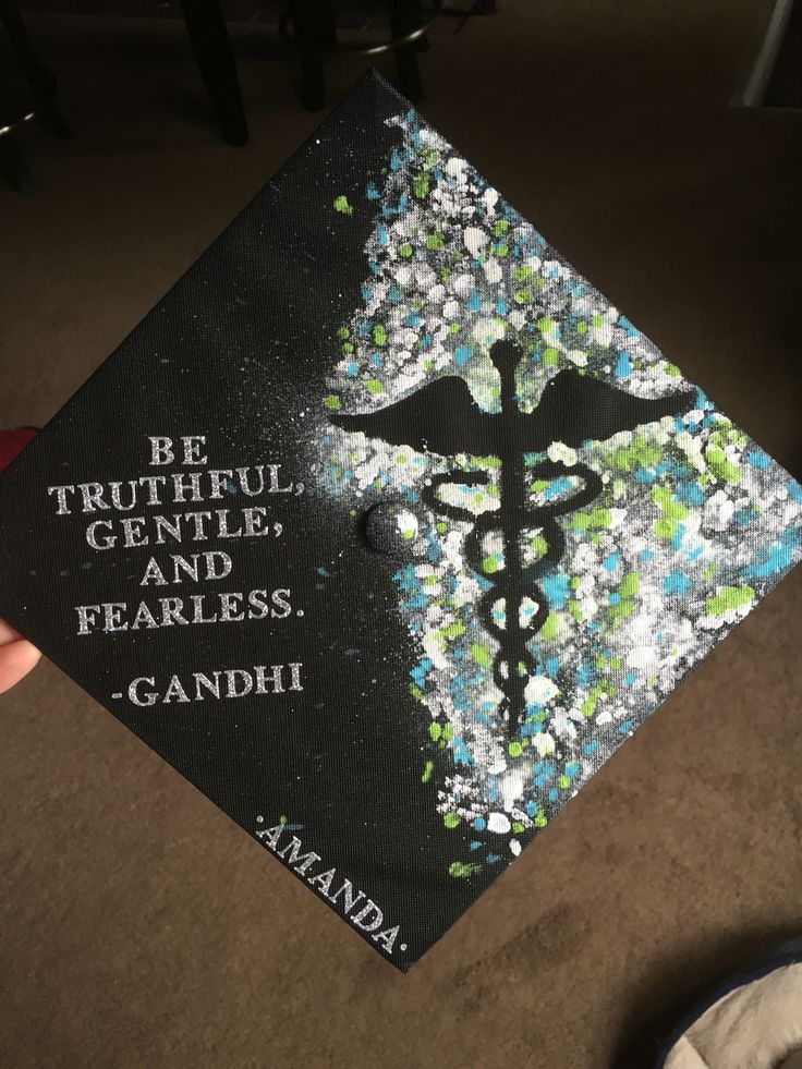 My nursing graduation cap decorated with a splatter paint caduceus and Gandhi quote.