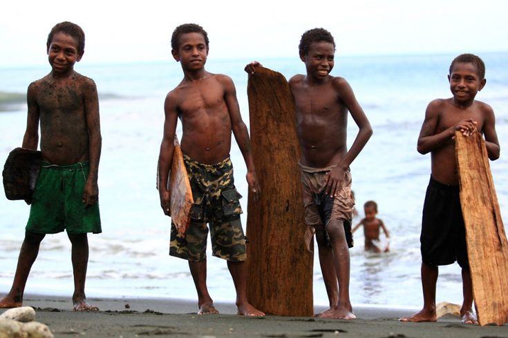young children in papua new guinea pose with their splinter surf boards carved from local trees or broken canoes Gudmundur 'Gummi' Fridriksson Blog http://www.gudmundurfridrikssonblog.com/undiscovered-waves-surfing-png/