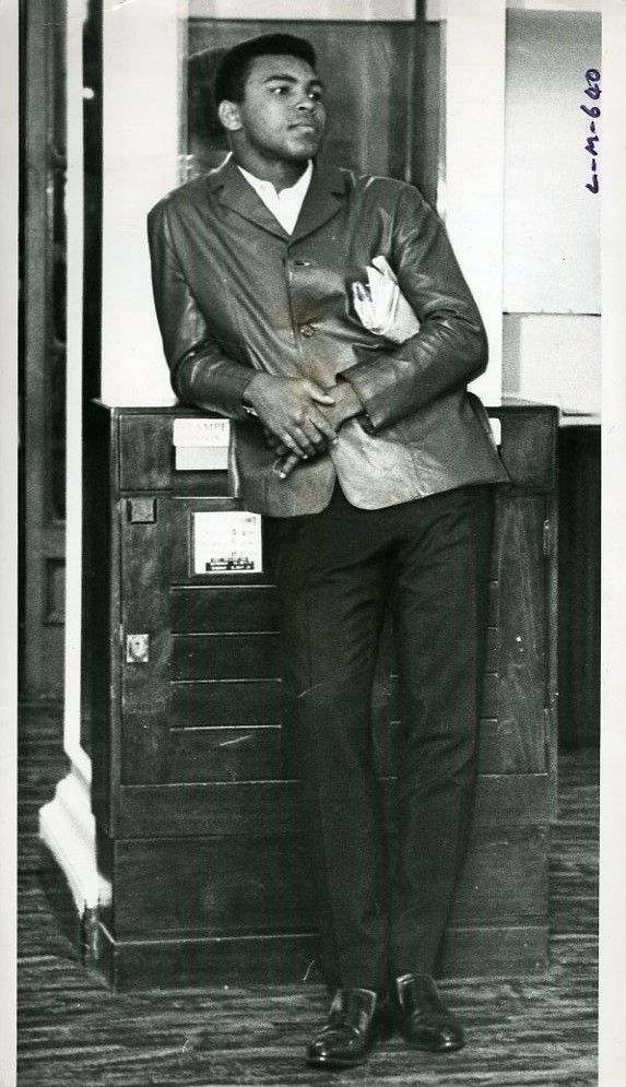 "Young World Heavyweight Champion Muhammad Ali (Cassius Clay) looks poised in this original 6.25 X 10.5 1966 wire photograph that is stamped and captioned on the verso ""Quiet Before the Battle,"" photographed at the entrance of the Piccadilly Hotel, London, May 20, 1966 on the day before his second meeting with Britain's Heavyweight Champion, Henry Cooper."