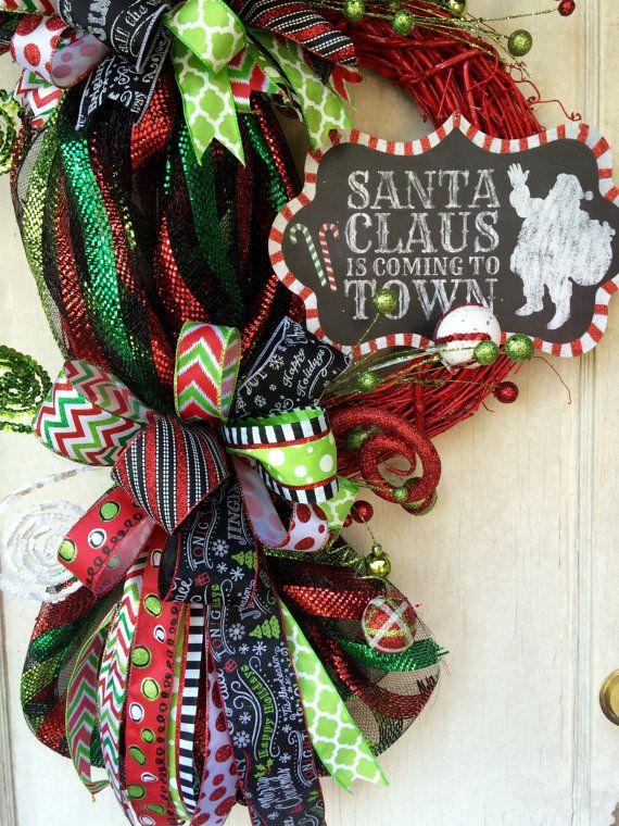 Il sagit dune maille de belle déco lunatique guirlande de Noël funky arc sur une base de vigne rouge. Il est noir rouge et citron vert avec des paillettes et plein déclat pioches et différents rubans. Il feautures un signe dardoise qui lit « Le père Noël arrive en ville ».  Voir plus de http://mrschristmasworkshop.etsy.com Articles