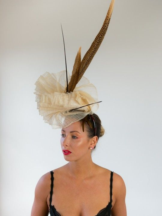 CHAMPAGNE TIFFANY | Hat/Fascinator for Caulfield Cup | FORD MILLINERY  $420  Hand-pleated vanilla sinamay, sculpted into one continuous double-fan that claims height and delicately touches the face. One ostrich quill spine orbits the centre, as the other stands tall fore contrast. Two glorious golden tail pheasant feathers (70-80cm) add even more height. Elegant, refined, and naturally glamourous.