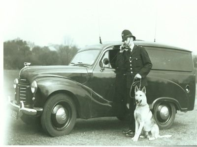 Terrific image that was taken sometime pre-1960 showing a Birmingham Police officer with police dog and vehicle.  West Midland Police UK