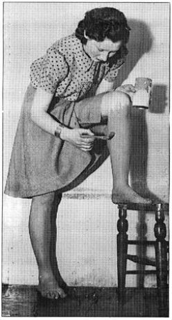 A young lady painting her legs with gravy browning to imitate stockings C.1940