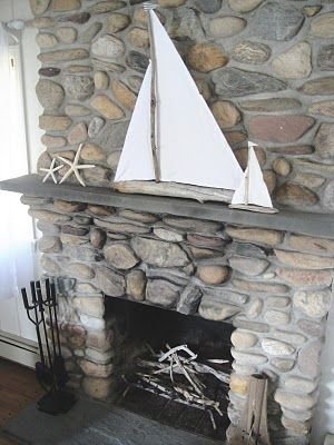 Beautiful white driftwood sailboat against the river rock fireplace by frugal farmhouse design