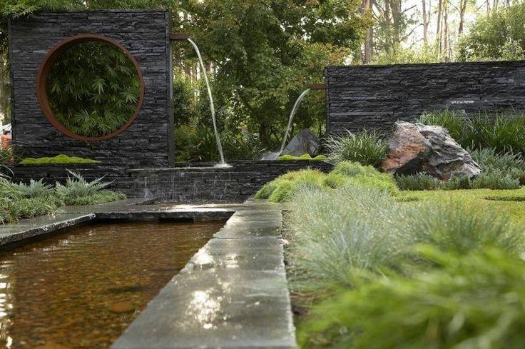 Gartenbrunnen mit Röhren in der Natursteinwand montiert