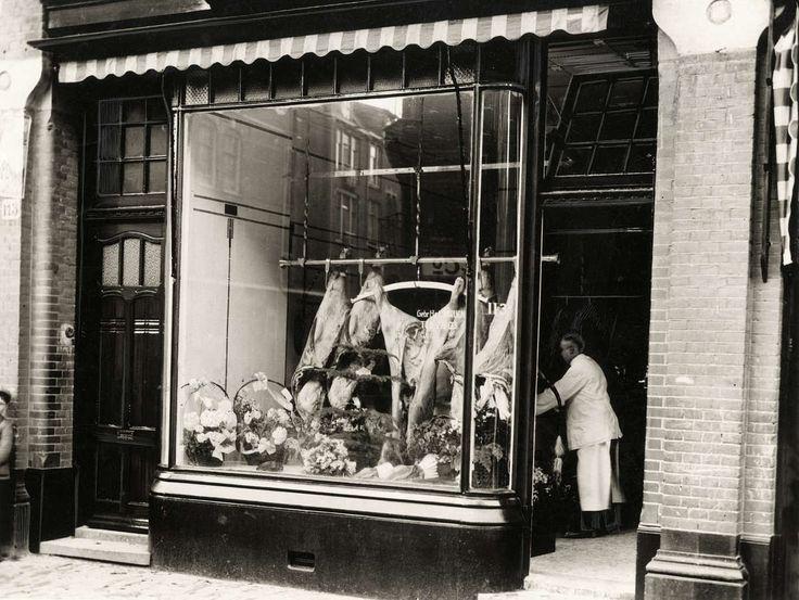 Buitenkant met etalage met karkassen vlees en bloemen erin van slagerij Baruch aan de Van Woustraat 113 in Amsterdam, met man in witte jas i...