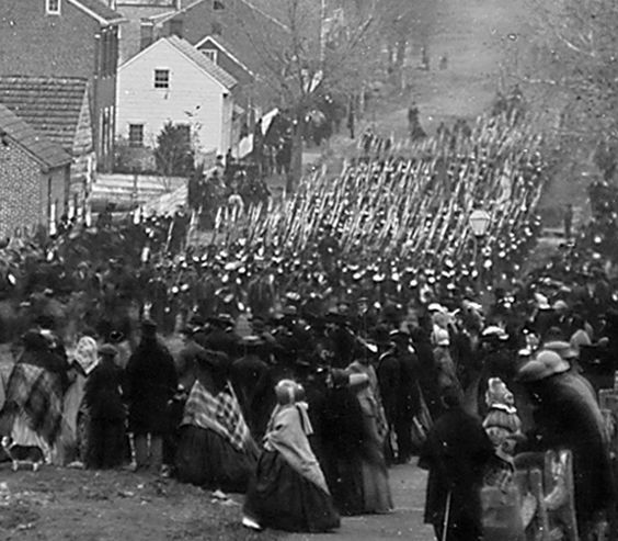 Troops marching in Gettysburg  Memorial Cemetery to see  President Lincoln make history by giving his Gettysburg Address.