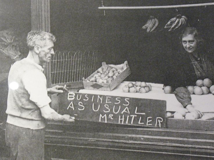 """A British shopkeeper hanging up a sign during the Blitz which reads, """"Business as usual Mr. Hitler.""""    London, England - 1940    (Photo by George Rodger)"""