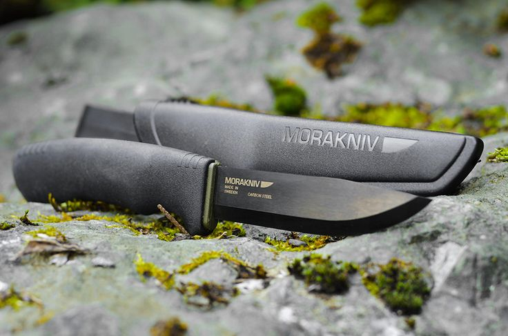 The Bushcraft Black from Morakniv of Sweden has a carbon steel blade and a black coating which protects against corrosion.  You can use the back of the blade with a fire starter. The spine of the blade is sharp, ground especially for that purpose.
