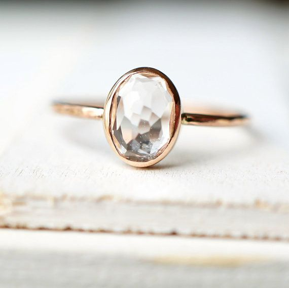 This ring made from solid 14k gold carries a rose-cut oval white topaz making it sparkly and unique. If you wear it on your night out, as your engagement ring or have it paired and layered with other