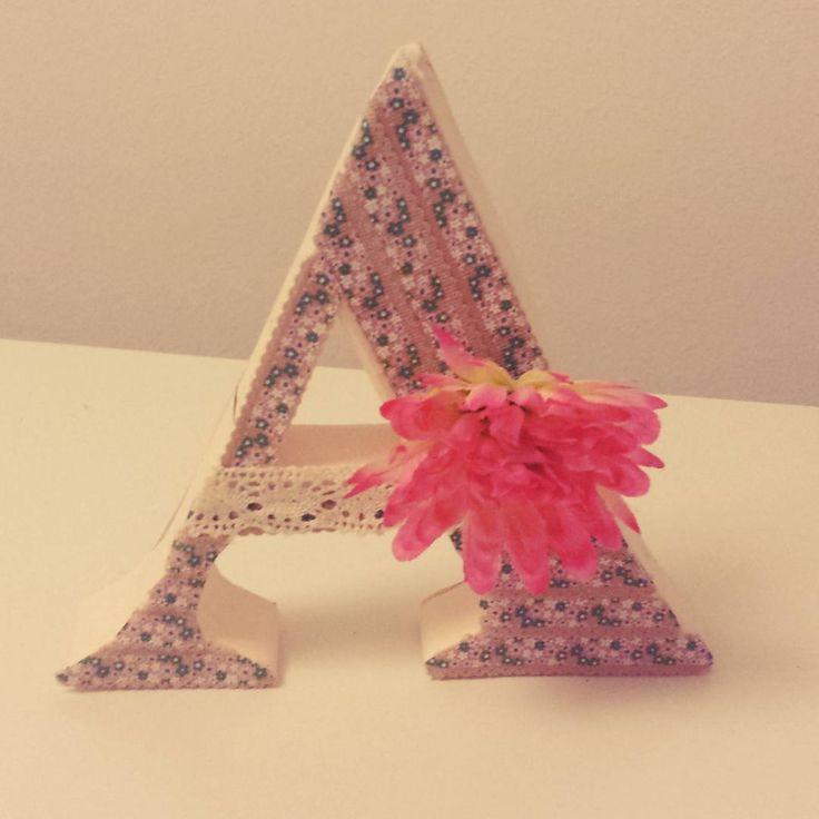 Letra hecha con cartón y cartulñina decorada con washi tape de tela , detalle de pasamanería y flor artificial.