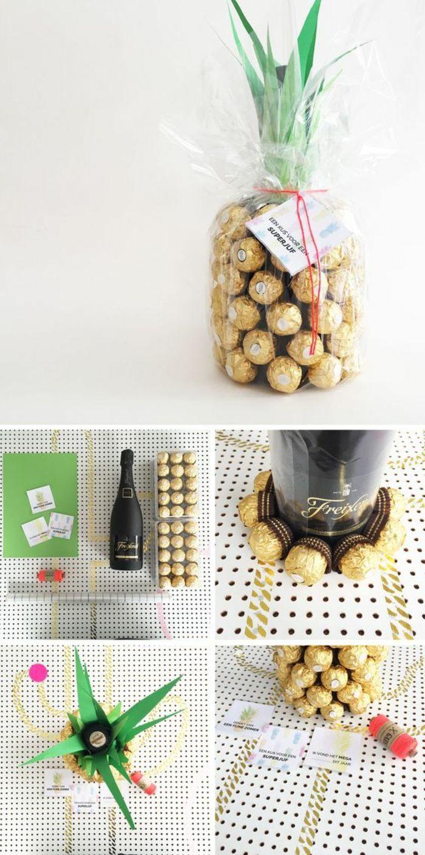Ananas aus Pralinen in goldenen Verpackungen, eine schwarze Sektflasche, einige