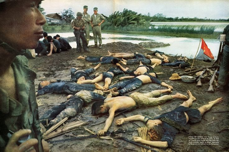 """Vietcong soldiers, trapped and shot down in the Delta, lie dead on a nearby shore beside their flag while captured comrades huddle in defeat. Americans in the picture were advisers to the Vietnamese."" 1963. ~ Vietnam War"