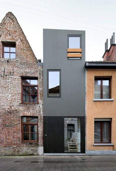Nowoczesna, prostopadłościenna bryła o gładkich, szarych elewacjach zdecydowanie kontrastuje z zaawansowanymi wiekiem sąsiadami, zwłaszcza z narożną, wzniesioną z cegły kamienicą nakrytą wysokim, dwuspadowym dachem. Mimo to, dzięki swojej minimalistycznej, spokojnej formie i dostosowanym do skali zabudowy gabarytom, nowy budynek nie staje się źródłem przestrzennego chaosu.  Architekci: Dierendonck Blancke Architecten Zespół projektowy: Alexander Dierendonck, Isabelle Blancke, Pieter Mouton