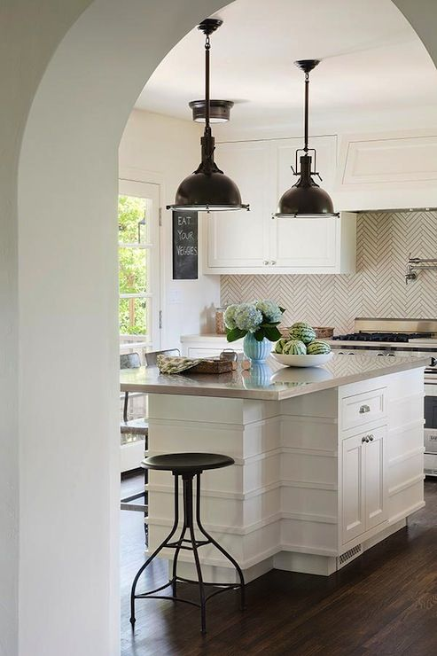Exquisite kitchen with creamy shaker cabinets paired with herringbone backsplash and gray countertops. Kitchen features Restoration Hardware Harmon Pendants in Dark Brass Natural over contemporary kitchen island with gray countertop lined with iron industrial stools.