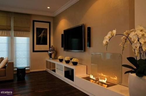 Sound bars hung vertically on both sides of a wall mounted flat screen TV