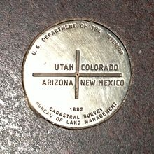"A metal disk reading ""U.S. Department of the Interior – Utah, Colorado, Arizona, New Mexico – 1992 – Cadastral Survey – Bureau of Land Management"""