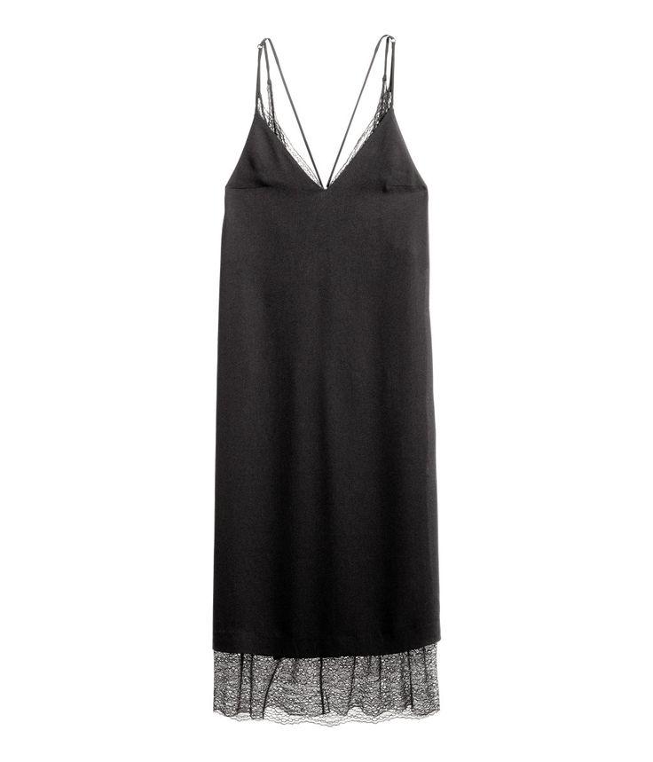 Sort. En v-ringet kjole i vevd kvalitet. Kjolen har bar rygg og smale skulderbånd som er korslagte bak. En underkjole med blonde øverst og nederst.