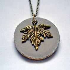 """Collier en béton rond """"Feuille d'Erable"""" - collection """"Couleurs d'automne"""" (par Sésé'Dille).    Ce collier est composé d'un pendentif rond en béton bordé de feuille de métal dorée, d'une breloque en métal dorée en forme de feuille d'Érable et d'une chaîne en métal dorée aspect vieilli."""