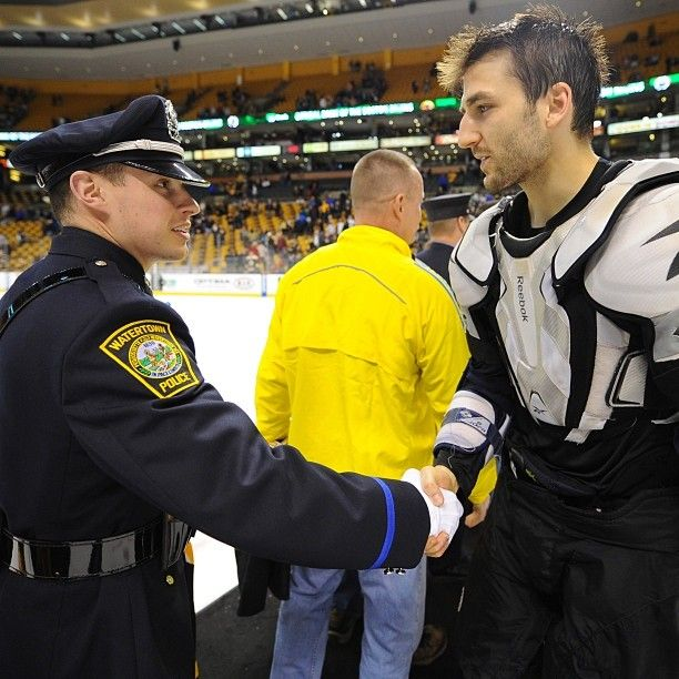 """4/21/13 Patrice Bergeron & a Watertown PD 1st responder shake hands during """"Shirts Off Their Backs"""" after the home game against the FL Panthers."""