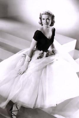 """I vestiti indossati nei film dall'attrice Grace Kelly, sono diventati icone della moda, uno dei costumi più celebri è il vestito bianco e nero creato dalla stilista Edith Head per """"La finestra sul cortile"""", con corpetto nero dal profondo scollo a """"V"""" sia sul décolleté che sulla schiena e con gonna bianca drappeggiata realizzata in strati di chiffon e tulle, e decorata sulla parte superiore da alcuni disegni di rami di albero."""