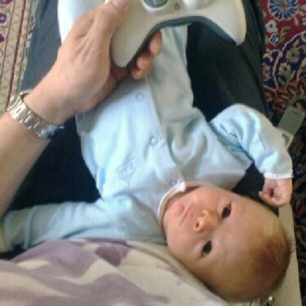 OMG a baby Louis laying on daddys lap while he plays Xbox! My heart just melted.