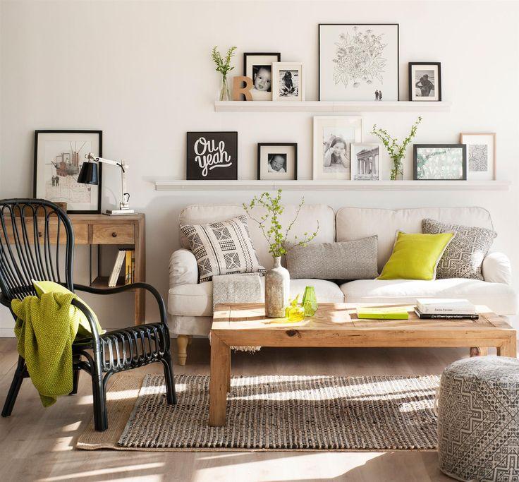 Salón con pared de cuadros sobre estantería fina, sofá gris y mesa de centro de madera_00433241