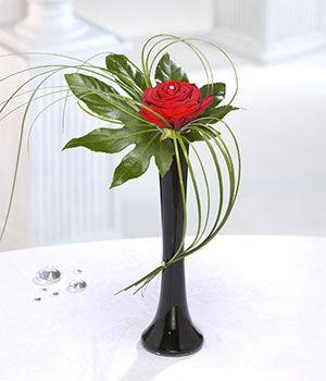 sola rosa roja entrega en un florero negro elegante