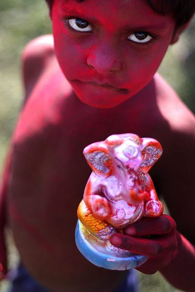 New Delhi, India: a young devotee holds a small statue of the elephant-headed Hindu god Lord Ganesh to immerse into the river Yamuna on the last day of Hindu Ganesh Chaturthi festival