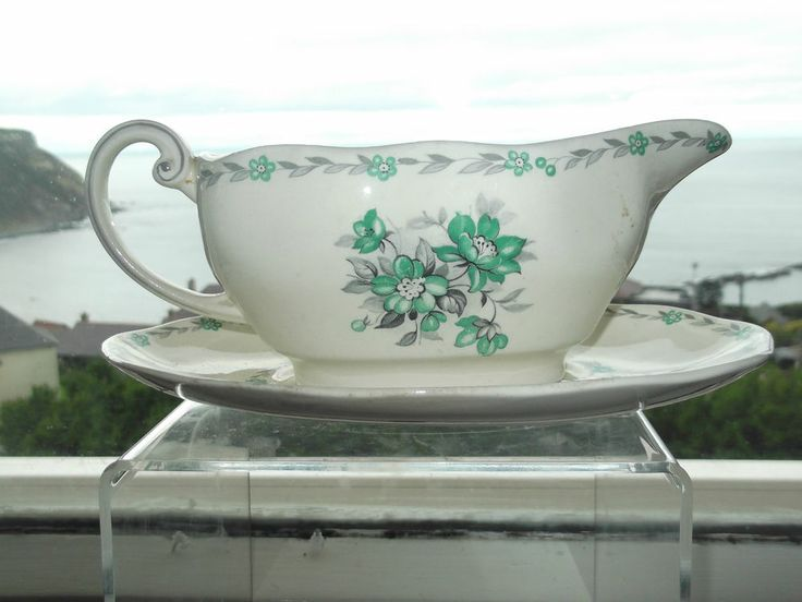 this is part of a dinner set by WEDGEWOOD AND CO the set is called hazel made in 1950 it is quite a rear set  An ivory glazed china gravy boat and saucer , decorated with a transfer-printed central posy of green flowers and grey foliage, with two wreath borders of green flowers and cherries with grey laurel leaves.