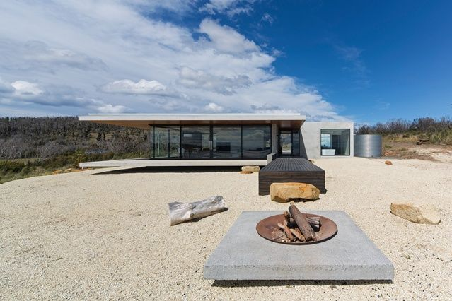 The pragmatic is mixed with the poetic, as precast concrete, steel and glass come together to form this robust holiday house perched on the Tasmanian coast.
